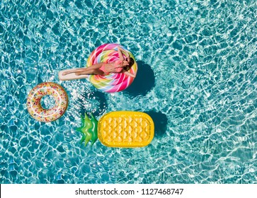 Beautiful, sportive woman in bikini relaxes on a lolli pop shaped swimming pool float during a hot summer day