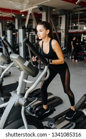 Beautiful sportive woman working on elliptical machine in jogging sneakers