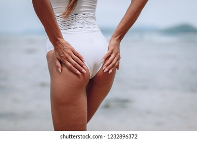 beautiful sports ass in the sand on the Blurred background in white swimsuit on the beach. Blurred background. Trips to warm destinations. Close Up. Phuket. Thailand.