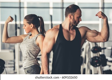 Beautiful sports couple is showing their muscles while standing in gym
