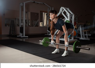 beautiful sports fitness girl with a barbell in the gym