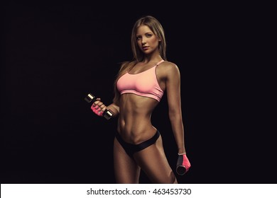Beautiful sports fitness sexy girl posing on black background