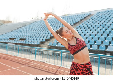 A beautiful sports girl in black sportswear is doing a warm-up before practicing sports at the stadium. The concept of a healthy lifestyle.