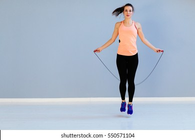 Beautiful sports girl doing exercises with jumping rope.