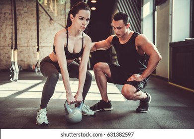 Beautiful sports girl is doing exercises with a kettlebell while working out with a personal trainer in gym