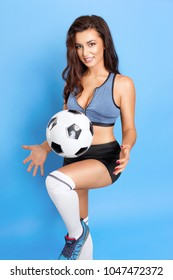 Beautiful sports girl posing with a ball as a football player on a blue background.
