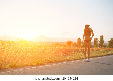Beautiful sports girl running along the field at sunset, female jogger resting after evening run at sunset, fitness and healthy lifestyle concept