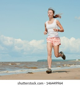 Beautiful sports girl runs along the beach.