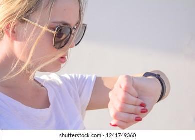 Beautiful sports girl is touching her fitbit bracelet after training