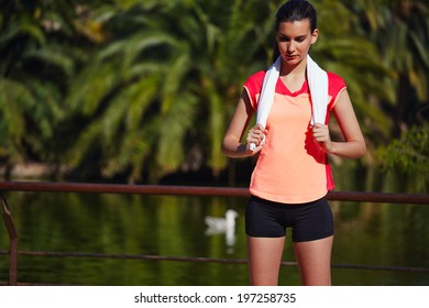 Beautiful sports girl with a towel around his shoulders resting after a morning run
