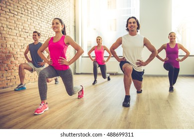 Beautiful sports people are doing exercises and smiling while working out in modern fitness hall