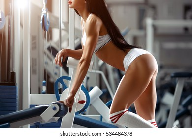 Beautiful sports young woman posing in fitness gym. Fitness girl in white sportswear. Muscular brunette fitness woman doing exercises in the gym. Sport - concept of healthy lifestyle.