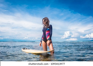 beautiful sportswoman in wetsuit standing at surfing board in ocean at Nusa dua Beach, Bali, Indonesia