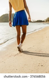 Beautiful sporty black girl in blue skirt walk at tropical ocean shore with golden sand. Outdoor lifestyle close up of female long legs in white converse sneakers. Sunny hot summer day. Swag, fashion.