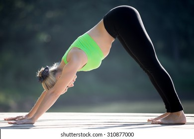 Beautiful sporty blond young woman working out outdoors on wooden deck, standing in downward facing dog posture, surya namaskar complex, full length