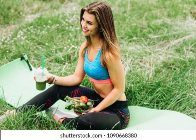 beautiful sporty caucasian woman drinking green smoothie from a plastic cup and breakfast with vegetables after morning exersices