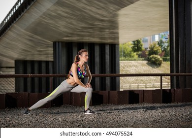Beautiful sporty caucasian woman stretching and preparing to run, urban background, Healthy lifestyle concept.