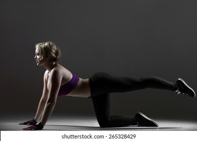 Beautiful sporty dancer girl in sportswear, warming up, doing leg swings, fitness exercises for buttocks, on black background, low key studio shot