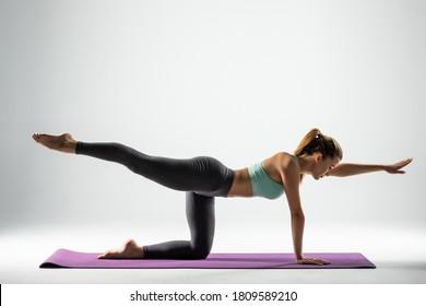Beautiful sporty fit woman practices Ashtanga Vinyasa Yoga asana Virabhadrasana 2 - warrior pose 2 isolated on white