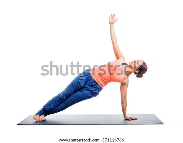 Beautiful sporty fit woman practices yoga asana Vasisthasana - side plank pose isolated on white
