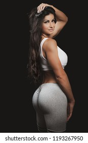 Beautiful sporty fit woman in studio on a black background. Young gym woman with long black hair. Perfect buttocks. The woman wears gray leggings and a white top.
