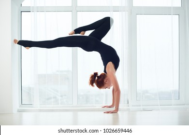 Beautiful sporty fit yogi redhead woman practices yoga handstand asana Bhuja Vrischikasana - Scorpion pose at the yoga studio.