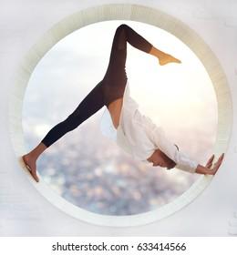 Beautiful sporty fit yogi woman practices yoga asana eka pada Adho Mukha Shvanasana - One Leg Downward Dog pose in a round window with a view of the city at sunset