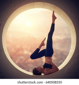 Beautiful sporty fit yogi woman practices yoga asana Salamba Sarvangasana - shoulderstand pose in a round window with a view of the city at sunset