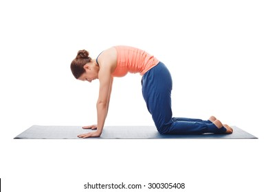 Beautiful sporty fit yogini woman practices yoga asana marjariasana - cat pose gentle warm up for spine (also called cat-cow pose) isolated on white