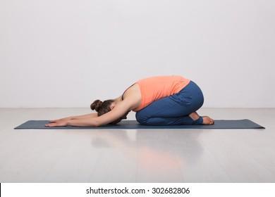 Beautiful sporty fit yogini woman practices yoga asana balasana (child's pose) - resting pose or counter asana for many asanas in studio