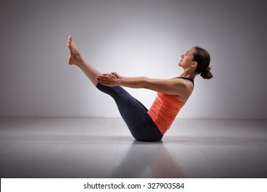 Beautiful sporty fit yogini woman practices yoga asana Paripurna navasana - boat pose