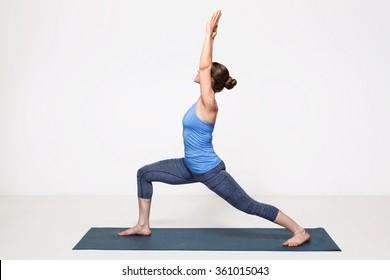 Beautiful sporty fit yogini woman practices yoga asana Virabhadrasana 1 - warrior pose 1