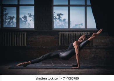 Beautiful sporty fit yogini woman practices yoga asana Eka Pada ardha Purvottanasana in the dark hall