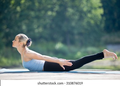 Beautiful sporty fit young woman in sportswear working out outdoors in park on summer day, doing Salabhasana, Locust Posture, Double Leg Kicks exercise, backward extension of the spine, full length