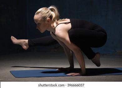 Beautiful sporty fit young woman working out indoors against grunge dark blue wall. Model doing handstand, arm balance, Eka Pada Bakasana 2, one-legged crane posture II. Full length