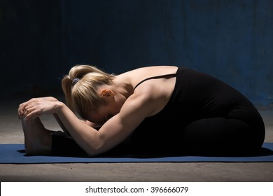 Beautiful sporty fit young woman working out indoors against grunge dark blue wall. Model doing Seated Forward Bend yoga pose, Paschimothanasana (Caterpillar - yin posture). Full length