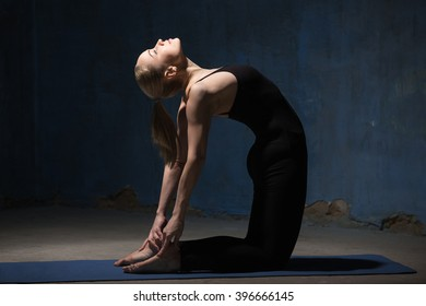 Beautiful sporty fit young woman working out indoors against grunge dark blue wall. Model standing on her knees, doing backbend exercise Ustrasana, Camel Posture. Full length
