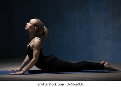 Beautiful sporty fit young woman in black sportswear working out indoors against grunge dark blue wall. Model doing cobra asana, bhudjangasana (Seal - yin yoga variation). Full length. Copy space