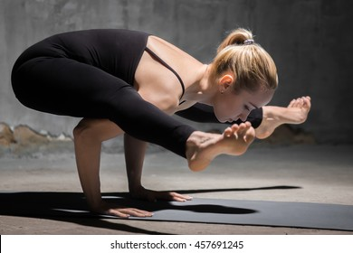 Beautiful sporty fit young woman working out indoors against grunge dark grey wall. Model doing handstand, arm balance, Firefly posture, asana Tittibhasana. Full length. Side view
