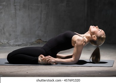 Beautiful sporty fit young woman working out indoors against grunge dark grey wall. Model sitting in Reclining Hero Pose - variation of Virasana or Supta-Vajrasana, Fixed Firm Pose (bikram)