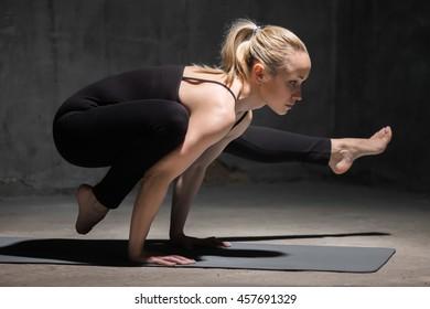 Beautiful sporty fit young woman working out indoors against grunge dark grey wall. Model doing handstand, arm balance, Eka Pada Bakasana 2, one-legged crane posture II. Full length