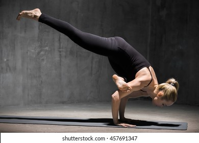 Beautiful sporty fit young woman working out indoors against grunge dark grey wall. Model doing arm stand exercise, Eka Pada Galavasana, Flying Pigeon (Flying Crow) Pose. Full length