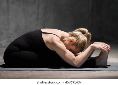 Beautiful sporty fit young woman working out indoors against grunge dark grey wall. Model doing Seated Forward Bend yoga pose, Paschimothanasana (Caterpillar - yin posture). Full length