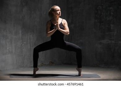Beautiful sporty fit young woman working out indoors against grunge dark grey wall. Model standing in Goddess, Temple or Sumo Squat Pose. Full length