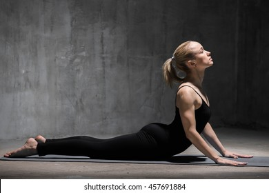 Beautiful sporty fit young woman in black sportswear working out indoors against grunge dark grey wall. Model doing cobra asana, bhudjangasana (Seal - yin yoga variation). Full length. Copy space