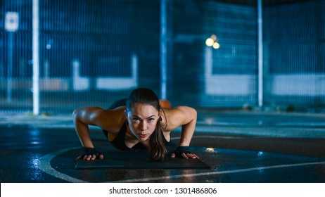 Beautiful Sporty Fitness Girl Doing Push Up Exercises. She is Doing a Workout in a Fenced Outdoor Basketball Court. Night Footage After Rain in a Residential Neighborhood Area.