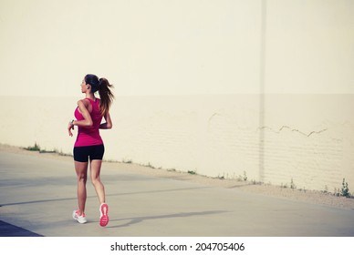 Beautiful sporty girl with muscular athletic body on the morning jogging at sunny day, female jogger runs along pastel color wall, ealthy lifestyle and fitness concept