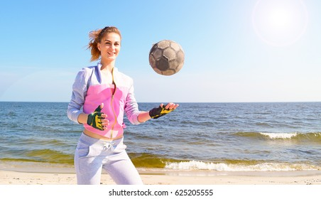 Beautiful sporty girl playing a soccer ball on background of ocean and sky