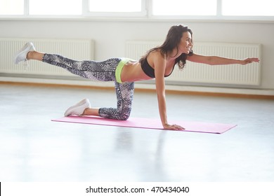 Beautiful sporty girl practices yoga, pilates, doing balance exercise bird dog, fitness training for spine and shoulders