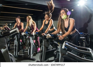 Beautiful sporty girls riding exercise bikes in gym.